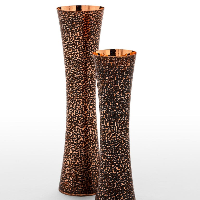 A stunning piece of decor, this set of two vases comprises two equal pieces in design but with different dimensions (H 37 x 10 cm, and H 30 x 10 cm). Boasting a unique silhouette, and an exquisite decoration contrasting a burnished polish to the