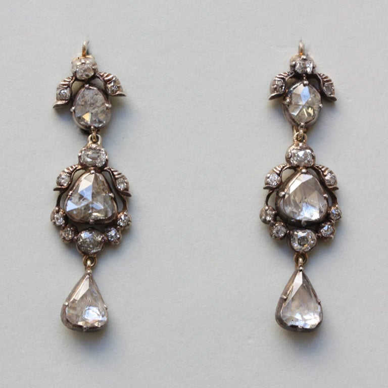 A pair of silver and gold earrings set with rose cut and cushion cut diamonds, gold hooks and gold backing, Dutch or German, 19th century.  weight: 7.08 grams dimensions: 4.5 x 1.3 cm