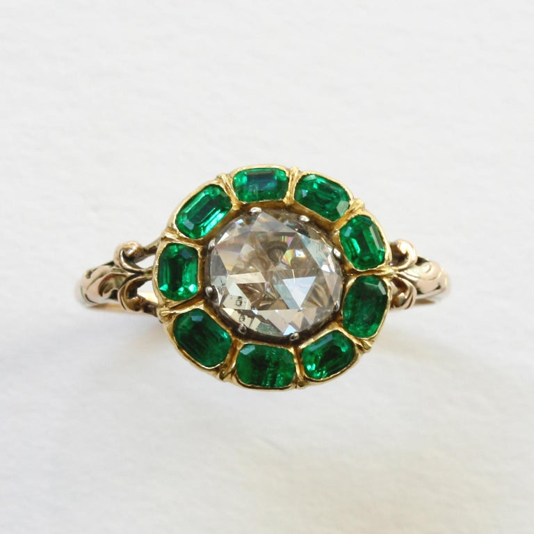 A gold ring with a large rose cut diamond (app. 1 carat) with 6 table cut emeralds around it (also app. 1 carat) in closed setting, circa 1760, England.  ring size: 16.75 mm / 6 ¼ US weight: 3.13 gram top dimensions: 13 x 12 mm width shank: 1- 5 mm.