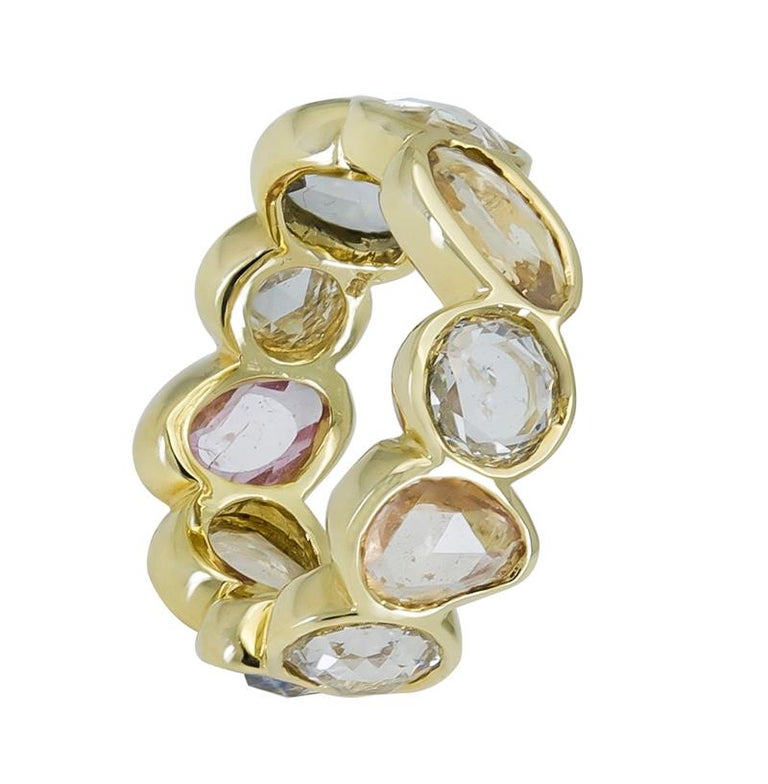 A unique eternity ring showcasing alternating mixed-shape rose cut sapphires and diamonds. Each stone is set in a polished bezel made in 18k yellow gold. Sapphires weigh 4.16 carats total and come in a variety of colors.  Diamonds weigh 2.60 carats
