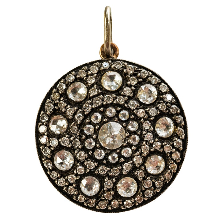 Recalling Ancient Muscovy or Mughal India densely set with co-centric bands of rose diamonds, mounted in silver and 9k rose gold, the reverse depicting stylized floral repoussé motifs.  With French control marks, chain not included.  1 1/4 in. (3.2