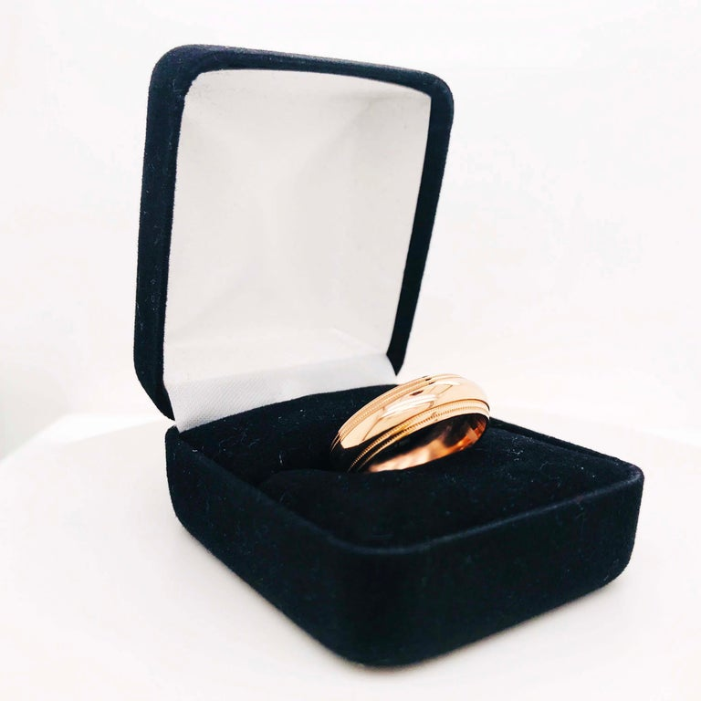 This custom rose gold band ring is a unique design with a classic structure. The band is a curved style (half round band) with a double beaded pattern near the edges of the ring. The band is 6 1/2 mm wide and made with a rich 14 karat rose gold! The