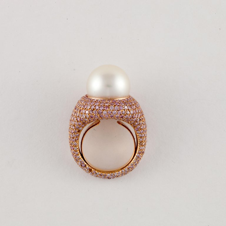 18K rose gold ring with large center South Sea pearl and pave' set pink diamonds.  The pearl measures 14mm.  The ring is encrusted with pink diamonds totaling 4.75 carats.  Ring is a size 6 with butterfly insert.  Presentation area measures 3/4