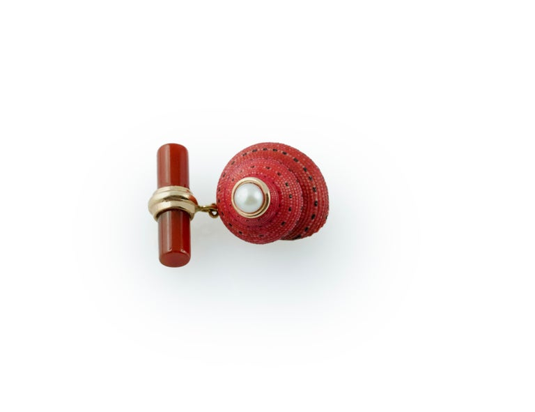 The striking red shade and natural texture of the  shell, adorned with a pearl at the top, is the protagonist of the front face of this elegant pair of cufflinks, which also features a cylindrical toggle in carnelian stone, whose red matches the one