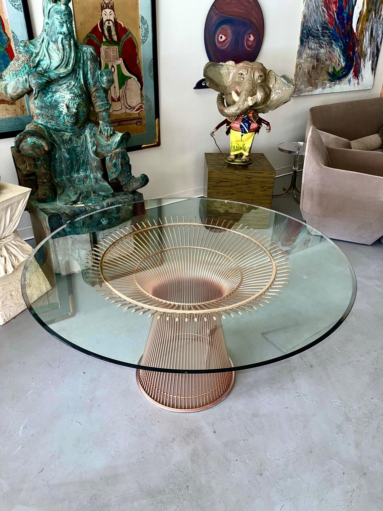 A beautiful rose gold Warren Platner for Knoll dining table. It is 53.75 inches in diameter. In excellent condition with a beveled edge facing down. Plastic/rubber guard on the base and rubber bumpers on four top pieces for protection. Purchased