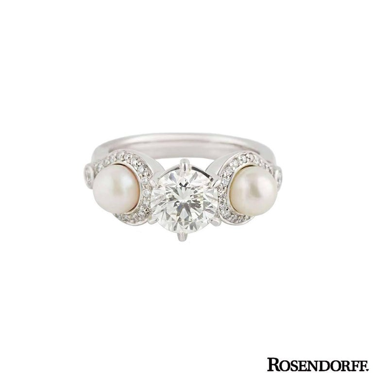 US size 4 5/8.  A beautiful 18k white gold diamond and pearl dress ring by Rosendorff. The ring is set to the centre with a 1.20ct round brilliant cut diamond, J colour and SI1 in clarity. The diamond is set in a six claw setting and is complemented