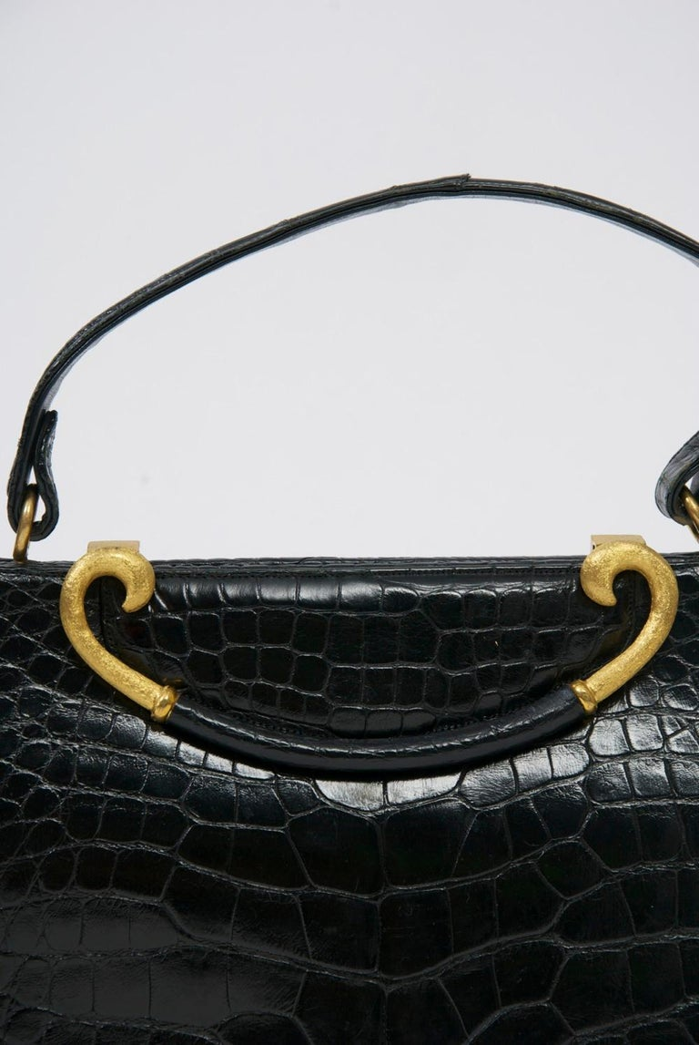 Classic 1960s handbag by Rosenfeld in black leather stamped to resemble alligator, its outstanding feature the curved clasp of brushed goldtone metal with leather center that lifts up to open the bag. The rich interior is of red leather with side