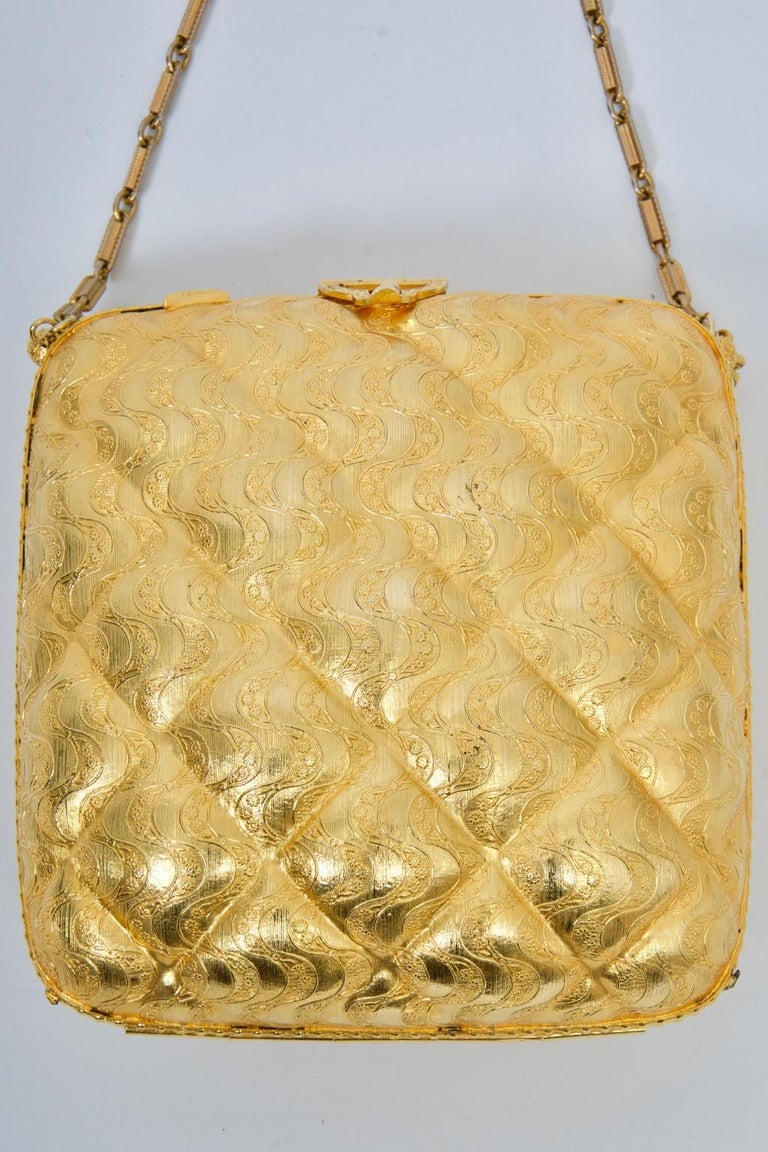 Rosenfeld c.1960s evening bag with chain of gold metal metal molded in a quilted and wave design. A gold metal triangular clasp, echoed on the reverse, secures the bag, while small gold tassels adorn the ends of the chain. Interior is coordinating