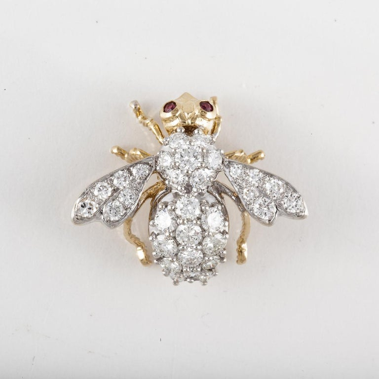 A bee pin in 18K yellow and white gold with diamonds and ruby accents.  The bee has two (2) ruby eyes and thirty-one (31) round diamonds that total 2.85 carats, G-H color and VS1-VS2 clarity.  The pin measures 1 1/4 inches by 1 3/16 inches.
