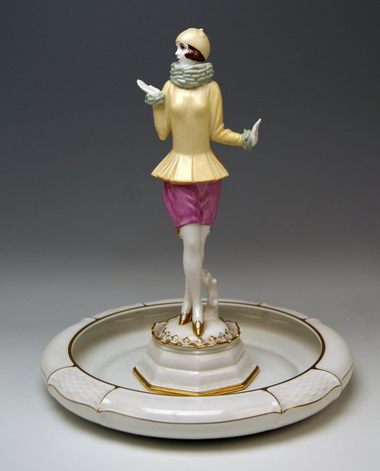 Lady Figurine 'YVONNE' Slim lady wearing cap stands upright, clad in very special costume: Tight yellow jacket and woollen scarf covering woman's neck and short lilac trousers (hot pants). The woman is wearing golden high heels, having her legs