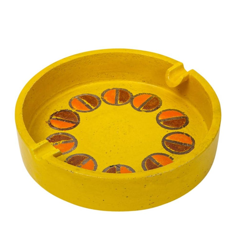Rosenthal Netter ashtray, ceramic, yellow and orange, discs, signed. Medium scale yellow glazed ashtray decorated with two rows of half circles, in dark and lighter shades of orange. Two trays for cigarettes. Signed with Rosenthal Netter label on