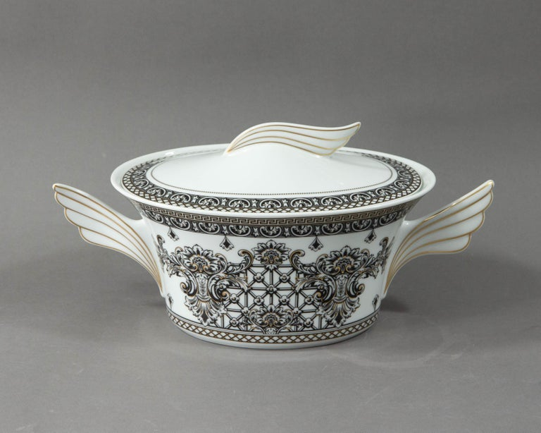 A lidded serving bowl or tureen made by Rosenthal belonging to the series Marqueterie, designed by Versace.  The form of the series is called Ikarus and was designed by Paul Wunderlich.  The series is decorated with attractive meandered gold