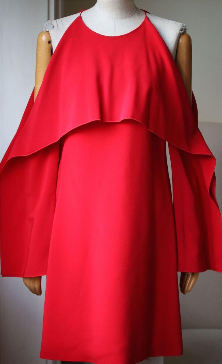 Rosetta Getty's collection is inspired by the iconic felt works of American conceptual artist Robert Morris. Made from stretch-cady, this dress has a draped overlay that folds over the bodice, cutout shoulders and wide, geometric sleeves. Red