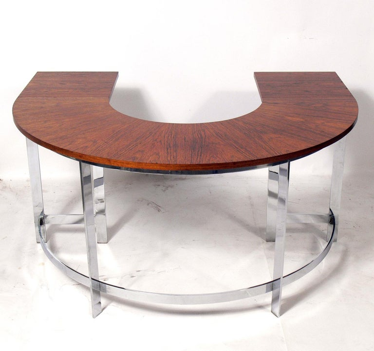 Rosewood and chrome arc desk and chair, circa 1960s. Very heavy and well made. The chair is currently being reupholstered and can be completed in your fabric at no additional charge. Simply send us two yards of your fabric after purchase. With the