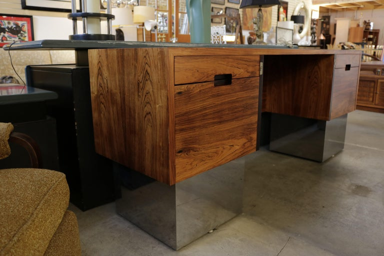 Beautiful rosewood grain narrow desk with chrome pedestals and inset handles and locks designed attributed to Milo Baughman. It can double as a console table because it is not as deep as most desks. It can also be used as a room divider since the