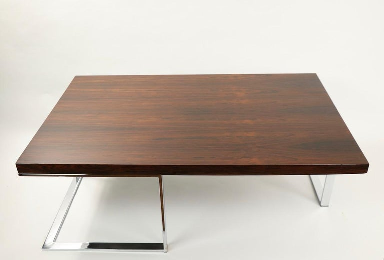 Chic and sophisticated rectangular coffee table having a thick rosewood (veneer) on opposing cantilevered chrome legs. This example is in good, original condition showing some signs of wear and use. Specific condition as follows: inconsequential