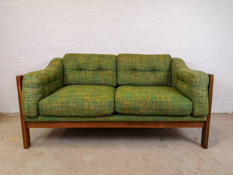 This 2-seat sofa made in Sweden for Futura Furniture in the 1960s, is made in rosewood and have green cushions seats.