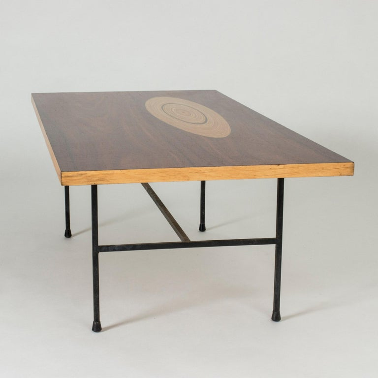 Stunning coffee table by Tapio Wirkkala, with a rosewood top inlayed with an oval shape of contrasting wood that has a growth ring-like pattern. Exquisitely restored. Sturdy base made from black lacquered metal.