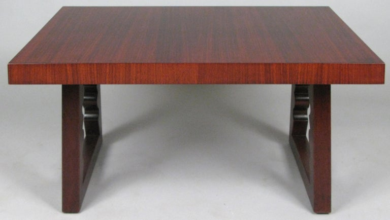 A beautifully detailed rosewood cocktail table designed by Andrew Szoeke, circa 1948. With a rectangular top and mahogany bases with sculpted details on the interior of the legs. Gorgeous rosewood graining.