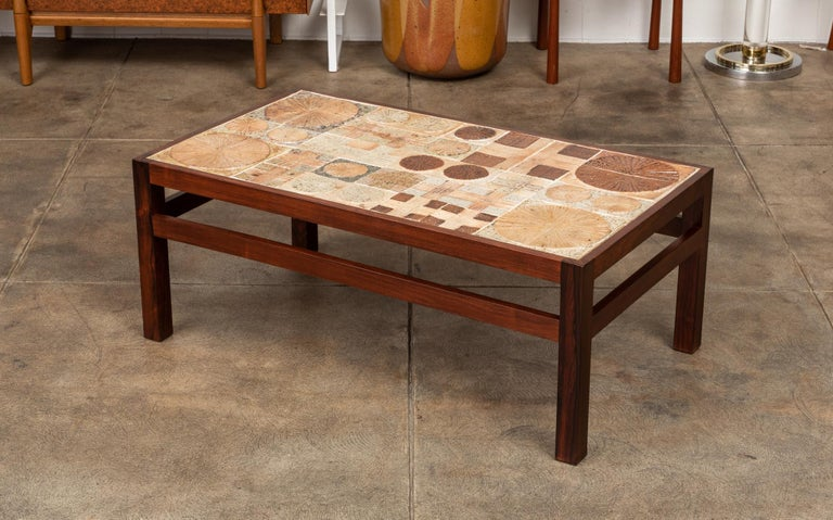Tile topped coffee table designed by Tue Poulsen & Erik Wörtz in Denmark, for Illums Bolighus during the 1960s. The rectangular rosewood frame and square legs were designed by Wörtz and the ceramic tiles were created by artist Tue