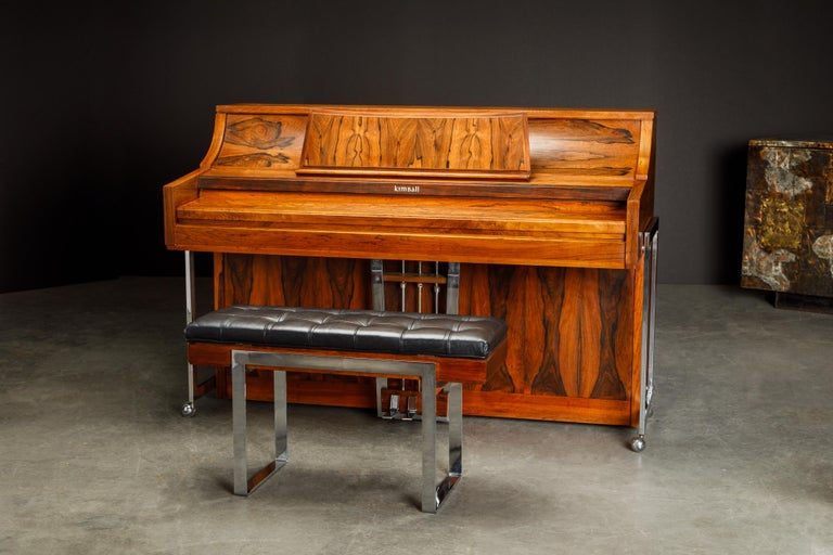 This incredible Rosewood piano is by Kimball, circa 1960s, and called the 'Artist Spinet' piano. We believe is the most attractive Mid-Century Modern piano we have seen, the Rosewood throughout the piano has gorgeous wood grain and color. Excellent