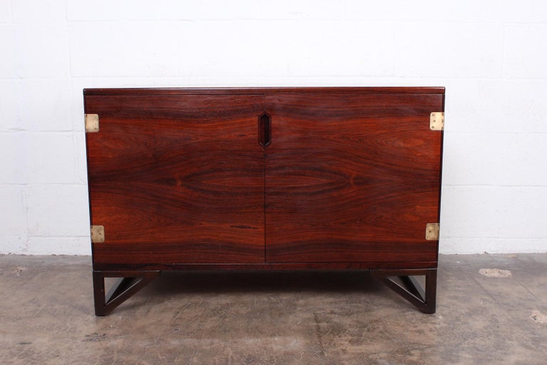 A rosewood cabinet with inset brass hinges and removable treys. Designed by Svend Langkilde.