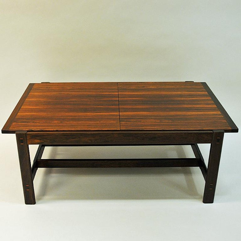 Magnificent and adjustable rosewood table for the livingroom. Designed by Torbjørn Afdal for Bruksbo 1962 and produced by Haug Snekkeri AS in the 1960s Norway. This smart table Sari has a black middle melamin plate to lenghten the table - or if