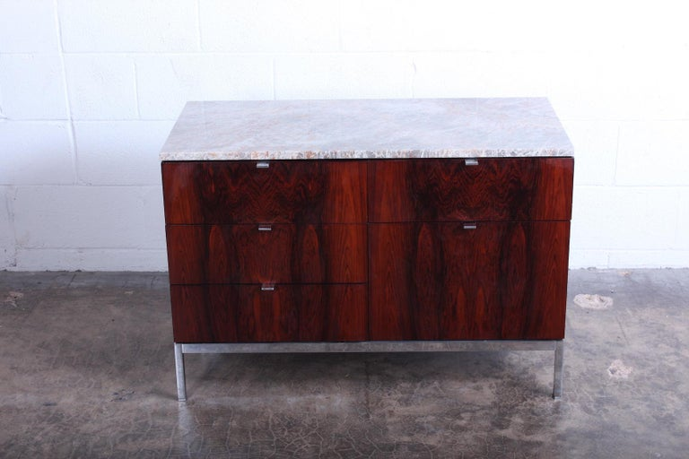 A rosewood credenza with chrome base and marble top. Designed by Florence Knoll for Knoll.