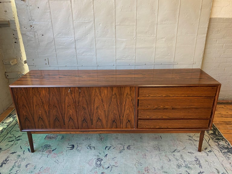A very handsome and well made credenza or sideboard made by the reputable furniture company Maurice Villency. The credenza features 4 drawers on the right side and a two-door storage compartment on the left, lined in sycamore veneers. The exterior