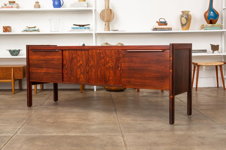 A stunning rosewood credenza, American, circa 1960s. The cabinet features a pair of highly figured rosewood sliding doors in the center of the piece with rosewood file drawers flanking either side. Both the doors and drawers have stylish sculpted