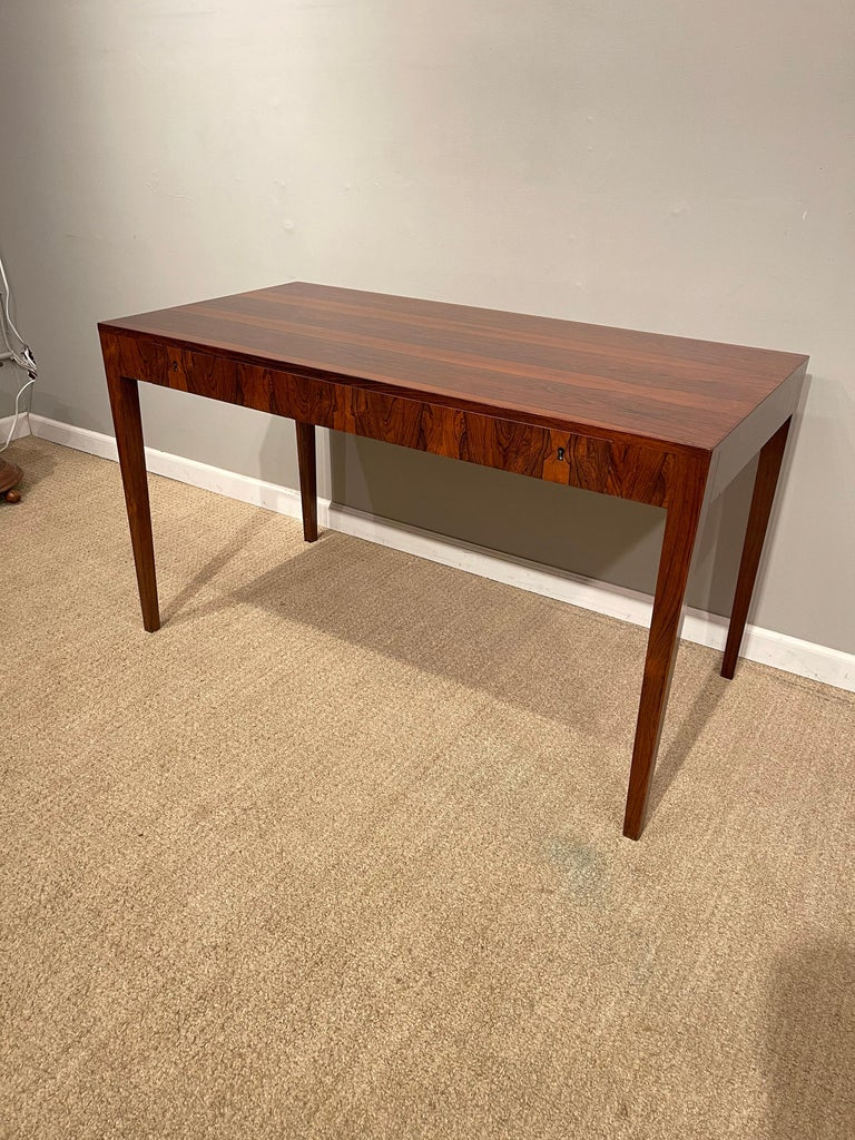A Rosewood Danish modern writing table, by Riis Antonsen with 2 drawers, 1 key.