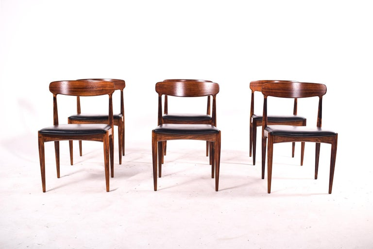 Set of six Danish rosewood dining chairs by Johannes Andersen for Uldum Mobler, 1960s. Upholstery in black leather. These chairs have high sculpted backs, two back posts integrated into the backs as one piece and the two front post on the chair