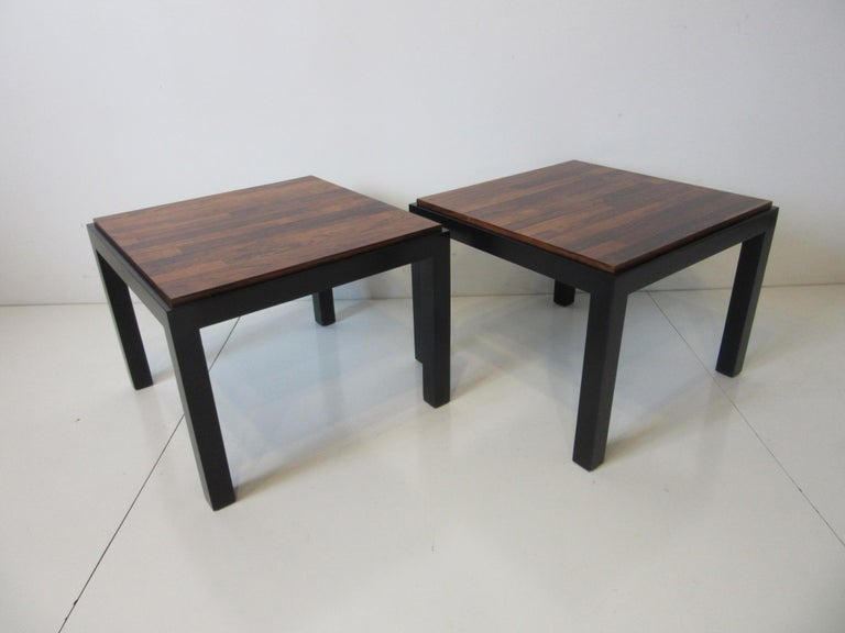 A pair of parson styled side tables with the bases in a dark ebony finish having drop in rosewood tops in the manner of Milo Baughman and the Thayer Coggin furniture company.