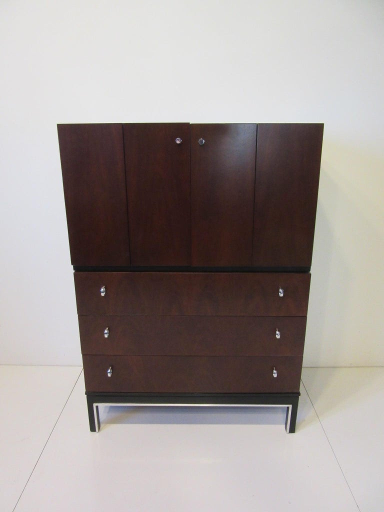 A well grained rosewood and ebony toned tall dresser chest with upper bi fold doors having storage sections and a drawer. The lower area has three drawers with chrome pulls and aluminum trim to the stretcher and leg area, retains the manufactures