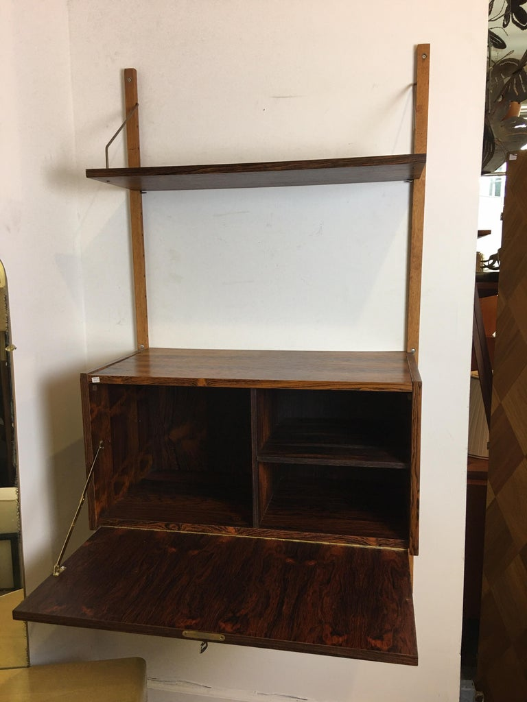 Very useful hanging rosewood wall unit, one bay wide. Adjustable cabinet and shelf. Perfect to use as a bar or entry piece! Rosewood is very clean, unit has 1 key, 2 wall brackets, 1 drop-front cabinet and 1 shelf. Cabinet is 15.5 deep, 31.5 wide