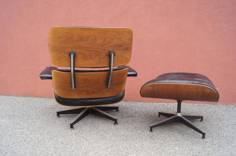 Charles and Ray Eames's classic lounge chair and ottoman for Herman Miller, models 670 and 671, exemplify deep comfort. A shell of molded rosewood veneer rests on a base of black enameled aluminum; the original down-filled cushions are upholstered