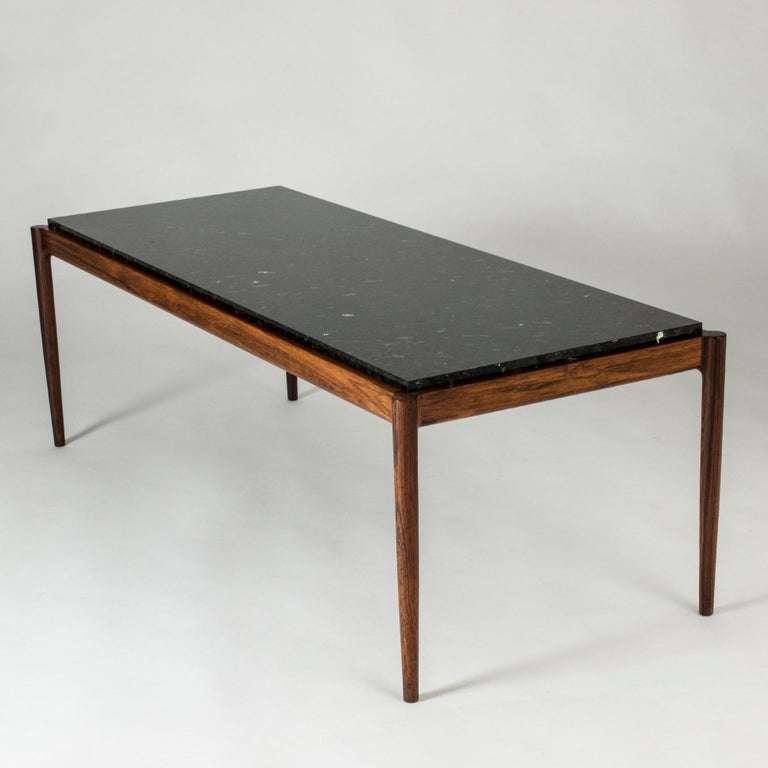 Elegant coffee table by Ib Kofod Larsen, with a rosewood frame and black marble table top. Smoothly rounded corners, subtle glimmer in the table top.
