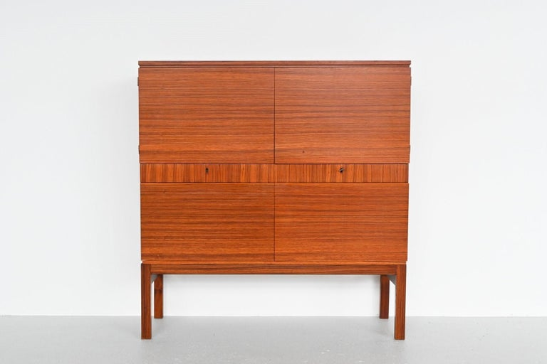 Beautiful shaped rosewood cabinet made in Belgium, 1960. It has plenty of storage space behind 2 doors at the top, 2 drawers in the middle and 2 drop-down doors at the bottom. The original key is still included. The cabinet is in very good original