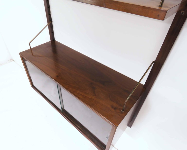 Rosewood single bay wall-mounted Royal System shelving unit, by Poul Cadovius, Denmark, circa 1960s. Consists of a single cabinet with glass doors (and interior glass shelf), and two adjustable rosewood shelves, one 7 7/8