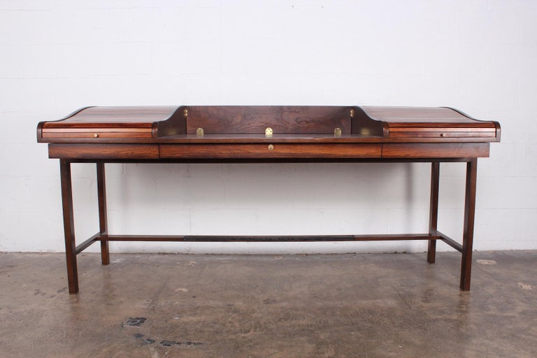 A rosewood tambour roll top desk with brass feet and leather trim. Designed by Edward Wormley for Dunbar.