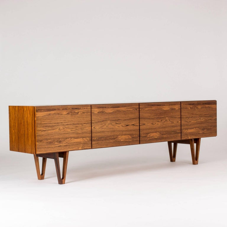 Stunning rosewood sideboard by Ib Kofod Larsen for the Swedish firm Seffle Möbelfabrik, made in the late 1950s. Long design that gives the impression that the sideboard is long. Beautifully sculpted legs and carefully hollowed out discreet handles.