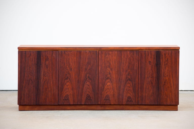 Midcentury rosewood sideboard from the 1960s. It is a shining example of the form and function synonymous with furniture of this era. It has is all, well-built, great design and heaviness. Four doors hiding storage space. The minimal design and the