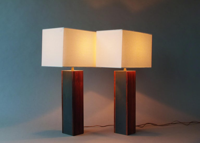 Handsome, elegant pair composed of solid rosewood and slate panels and original brass accents. Newer cotton shades, candelabra base sockets, and rotary line switches. The rosewood panels are 1/2