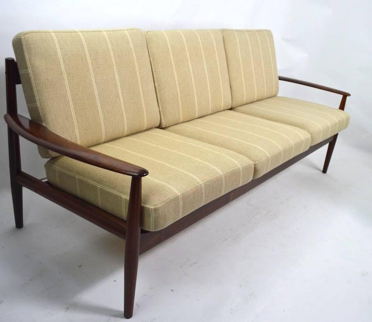 Wonderful rosewood Danish modern sofa designed by Grete Jalk for France and Son. This example is completely original, clean and ready to use. Truly an iconic example from the Golden Age of Modern Danish furniture. Measures: Arm height 21 inches x