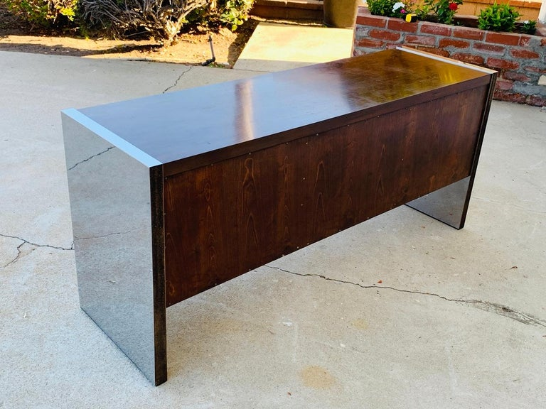 Roger Sprunger for Dunbar rosewood and stainless steel executive credenza dating from the early 1970s.   The credenza has generous storage having 2 file cabinets and 3 center drawers.  Measurements: 61 inches wide x 18.25 inches deep x 27.5