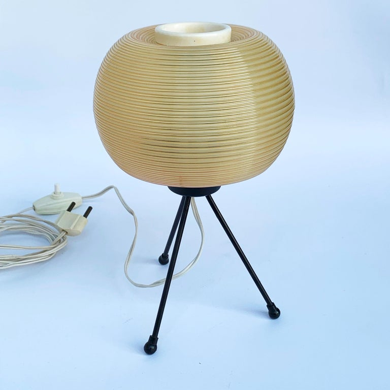 Lamp designed in a very rare style of the french 50s. The creator is Pierre Guariche (1926-1995), Editor: Disderot Base in black metal tripod. Support a rotaflex diffuser. E27 light bulb. Push-button switch. Bibliography: The Household Art