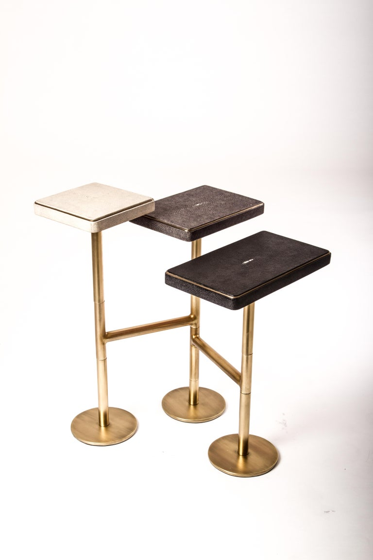 The 3-top rotating side table in cream shagreen, grey-blue shagreen and black shagreen is completely mobile, allowing one to adjust the piece to their preference from elongated to clustered. The shagreen inlaid tops have a discreet metal border