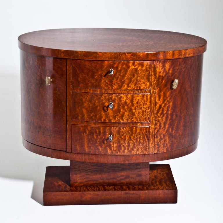Small Art Deco sideboard or nightstand veneered in thuja wood. The oval corpus with three drawers and two doors is mounted on a rotating base.