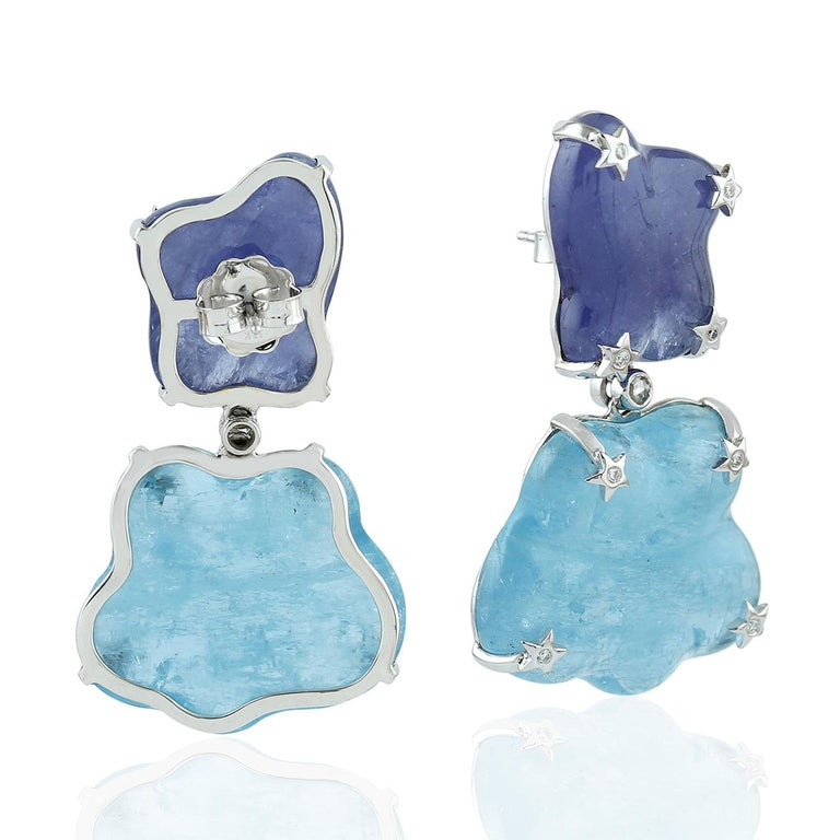 One of a kind this free-form Aquamarine & Tanzanite Earring in 18K white gold with star diamond motifs is like carrying those clouds around you. It's just majestic.  18KT: 11.655gms Dimond:0.25cts AQUMARINE: 54.97cts TANZANITE: 53.76cts