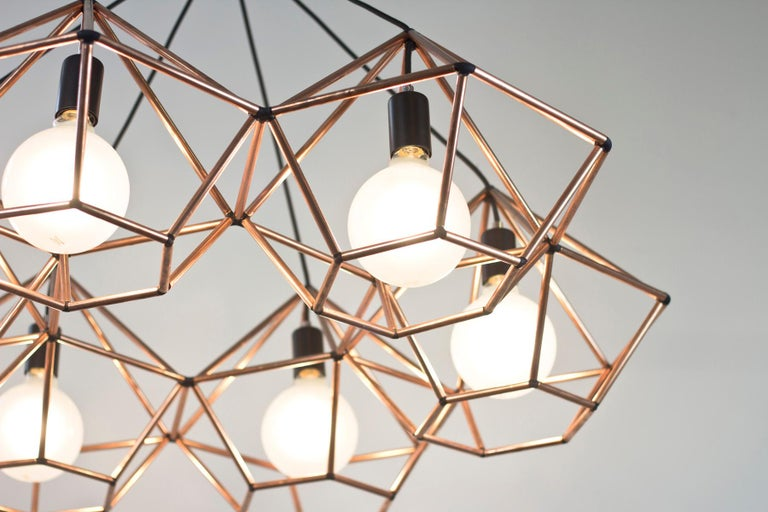Rough diamond chandelier is a decorative fixture that combines handmade craftsmanship with digital technology. The design combines a 3D printed joining system with hand cut and assembled copper or brass tube. The result is a decorative feature light